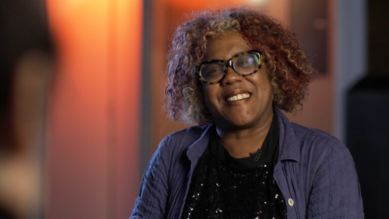 Errollyn Wallen being interviewed. She is smiling, wearing a black top with a sequin detail that catches the light, purple shirt and leopard print glasses.