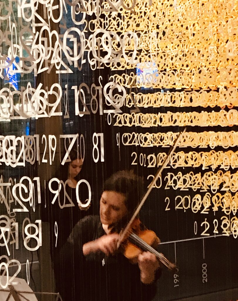 A blurred image of woman playing the violin standing underneath an Emmanuelle Moureaux's Slices of Time art installation - hundreds of golden numbers suspended in the air.