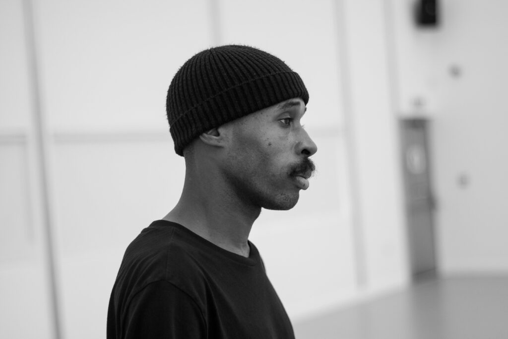 Theo TJ Lowe is pictured from the shoulders up looking off camera so we see his profile. He wearing a black tshirt and black beanie hat, and the blurred background looks like it could be a rehearsal room.